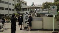 「入学式」看板を挟んで記念撮影